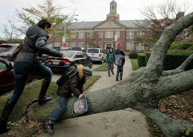 A woman and her son scramble over a tree toppled by Superstorm Sandy as she accompanies him to Public School 195, background, in the Manhattan Beach neighborhood of the Brooklyn borough, Monday, Nov. 5, 2012 in New York. Monday was the first day of public school for New York City students following the storm of a week ago. The woman declined to provide their names. Photo: Mark Lennihan, Associated Press / AP