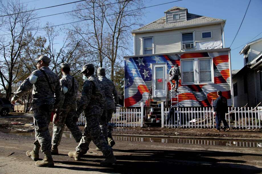 Members of the National Guard walk past a house damaged by Superstorm Sandy as it is painted with an American flag in the New Dorp section of Staten Island, New York, Tuesday, Nov. 6, 2012. Voting in the U.S. presidential election is the latest challenge for the hundreds of thousands of people in the New York-New Jersey area still affected by Superstorm Sandy. Photo: Seth Wenig, Associated Press / AP