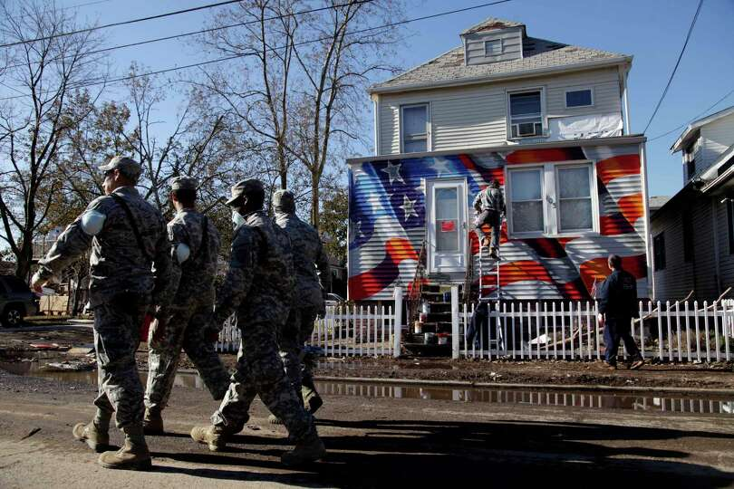 Members of the National Guard walk past a house damaged by Superstorm Sandy as it is painted with an
