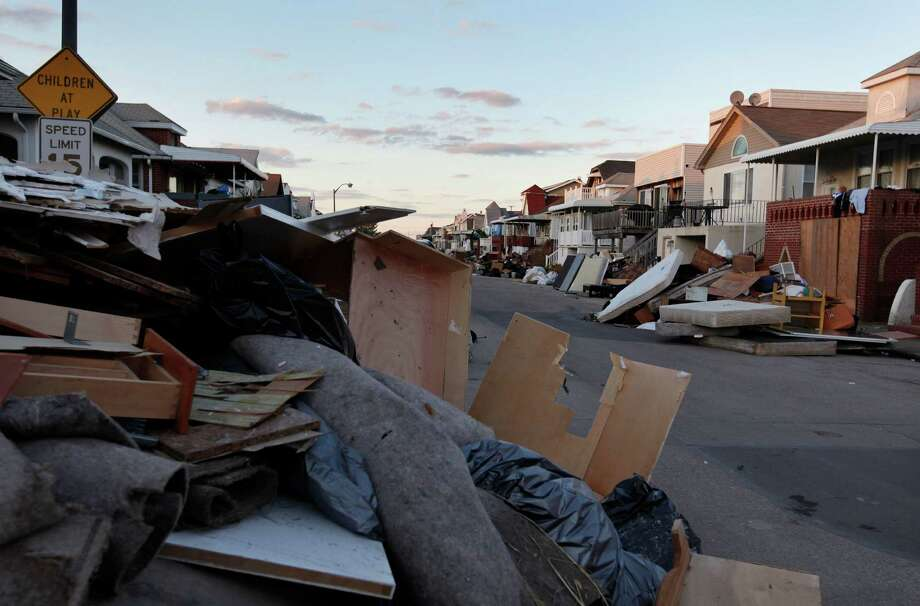 In this Monday, Nov. 5, 2012, photo, items discarded from homes damaged by Superstorm Sandy line a street, in Long Beach, N.Y. Temperatures dipped toward freezing early Monday, and tens of thousands of people without power along the ravaged Atlantic coastline faced the prospect of finding somewhere else to stay. Photo: Jason DeCrow, Associated Press / FR103966 AP