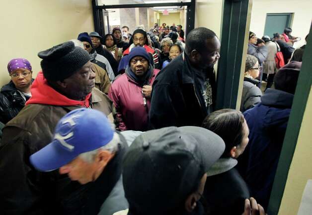 Voters crowd an apartment building hallway as they wait to enter a temporary polling station, right, Tuesday, Nov. 6, 2012 in the Coney Island section of New York. The building is hosting a voting station that was closed due to Superstorm Sandy. Photo: Mark Lennihan, Associated Press / AP
