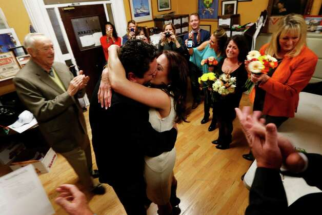 Thomas Carroll, 48, of Hoboken, N.J., center left, gives a kiss to his new bride, Stephanie McClure, of Smyrna, Ga., as a small party cheers for them moments after they were married by city clerk James Farina at Hoboken City Hall, Tuesday, Nov. 6, 2012, in Hoboken, N.J. The couple was scheduled to get married on Nov. 3, in Point Pleasant, N.J., but Superstorm Sandy washed away their wedding. Meanwhile, residents of Hoboken voted in the presidential election on Election Day in a polling place located in the adjacent room. Photo: Julio Cortez, Associated Press / AP