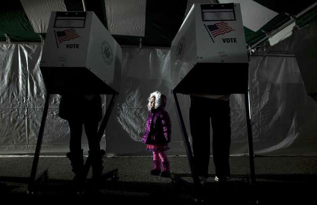 3-year-old Fiana waits for her parents to vote in the presidential elections in a tent in Midland Beach November 6, 2012 in the Staten Island borough of New York City. As Staten Island continues to recover from Superstorm Sandy, a few polling stations have been relocated due to power outages or ongoing use as an evacuation center. Photo: Allison Joyce, Getty Images / 2012 Getty Images