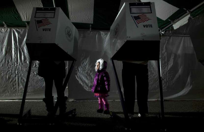 3-year-old Fiana waits for her parents to vote in the presidential elections in a tent in Midland Be