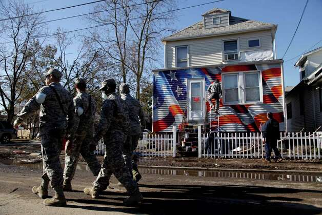 Members of the National Guard walk past a house damaged by Superstorm Sandy as it is painted with an American flag in the New Dorp section of Staten Island, New York, Tuesday, Nov. 6, 2012. Voting in the U.S. presidential election is the latest challenge for the hundreds of thousands of people in the New York-New Jersey area still affected by Superstorm Sandy.  (AP Photo/Seth Wenig) Photo: Seth Wenig