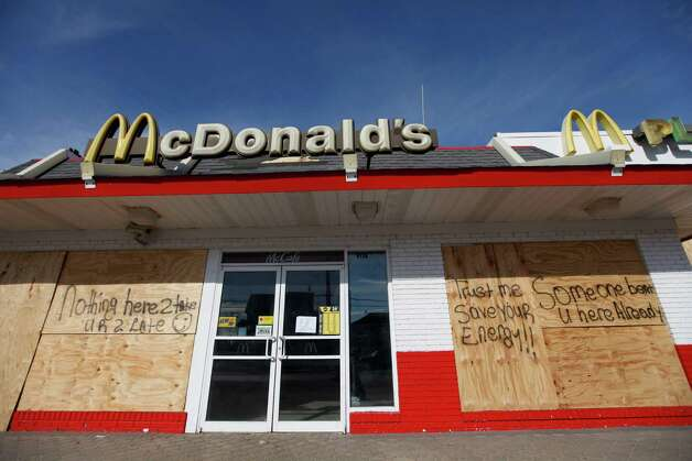 Messages discouraging looters appear on a boarded-up restaurant in Rockaway Beach, Tuesday, Nov. 6, 2012, in the the Queens borough of New York. Weather experts have some good news for beleaguered coastal residents in the Northeast: A new storm that threatened to complicate Hurricane Sandy cleanup efforts now looks like it will be weaker than expected.  (AP Photo/Jason DeCrow) Photo: Jason DeCrow