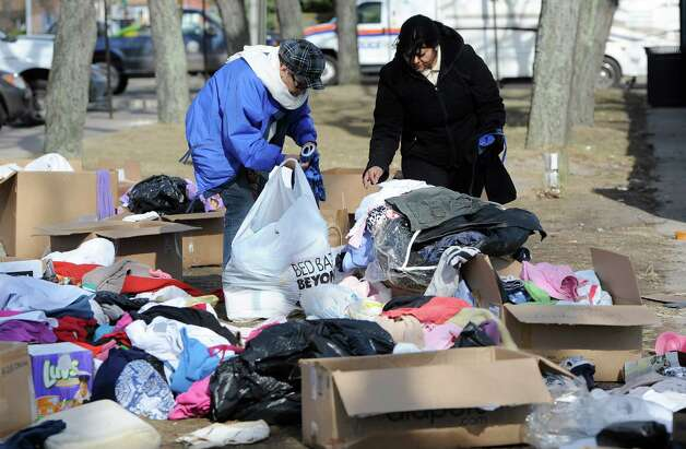 Two women look through piles of clothing in front of Long Beach city hall donated for victims of Superstorm Sandy on Tuesday, Nov 6, 2012, in Long Beach, N.Y. (AP Photo/Kathy Kmonicek) Photo: Kathy Kmonicek