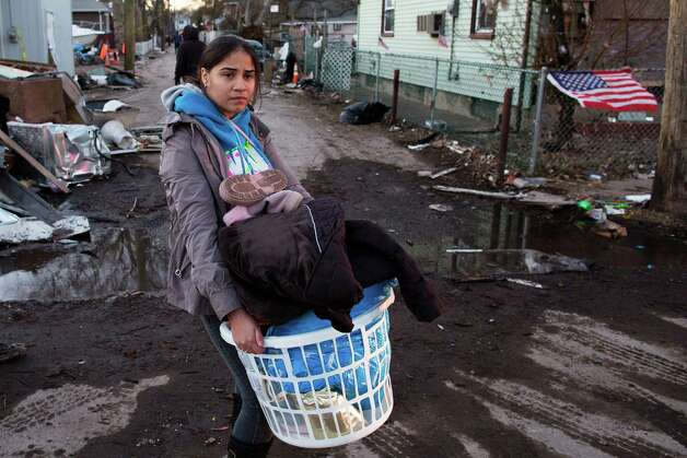 A resident of Staten Island's New Dorp Beach neighborhood carries a basket full of clothes and other items on her street that was devastated by Superstorm Sandy, Monday, Nov. 5, 2012, in New York. Although many areas of the metropolitan area are beginning to return to normal, neighborhoods of Staten Island's southern shore remain without power as the cleanup continues. (AP Photo/ John Minchillo) Photo: John Minchillo
