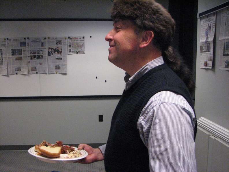"Art Director Tom Palmer proudly mugs with his coonskin cap. ""Hat Night"" is another electio"