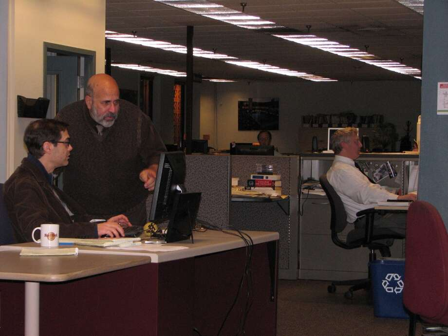 Timesunion.com Executive Producer Paul Block, standing, checks in with Web Producer Tim Neff early in the evening.