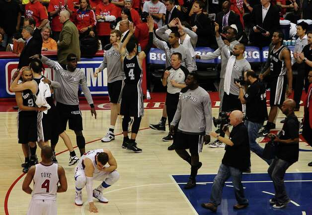 The Spurs celebrates as Los Angeles Clippers' Blake Griffin (bottom left) contemplates the loss of game four of the Western Conference semifinals at the Staples Center in Los Angeles on Sunday, May 20, 2012. The Spurs defeated the Clippers, 102-99. Kin Man Hui/Express-News Photo: Kin Man Hui, SAN ANTONIO EXPRESS-NEWS / San Antonio Express-News