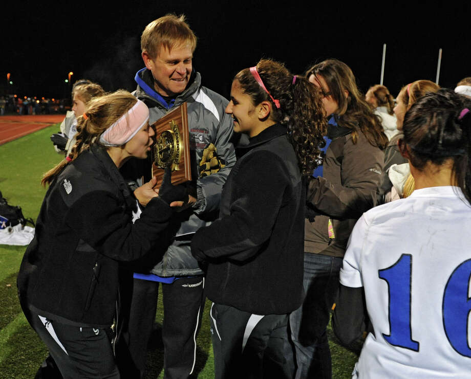 Hoosick Falls player Grace Delurey kisses the plaque after handing it to coach Tom Husser as the team celebrates winning the Class C Section II girls' soccer final against Mechanicville on Tuesday, Nov. 6, 2012 in Stillwater, N.Y.  (Lori Van Buren / Times Union) Photo: Lori Van Buren