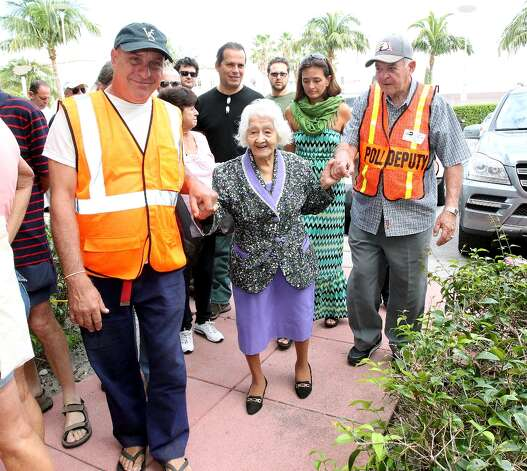 Isabel Castaño Restrepo, 106 years old, from Colombia, walks with the assistance of polling workers Albert Poledri and Nestor Pino, left to vote in Miami Beach Public Library on Election Day, Tuesday, Nov. 6, 2012. (AP Photo/El Nuevo Herald, David Santiago) Photo: David Santiago, Associated Press / El Nuevo Herald