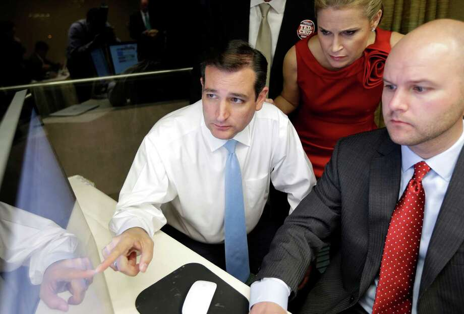 Republican candidate for U.S. Senate Ted Cruz, left, goes over election results with his wife Heidi, center, and campaign chief consultant Jason Johnson, right, Tuesday, Nov. 6, 2012, in Houston. Cruz is running against Democrat Paul Sadler to replace retiring U.S. Sen. Kay Bailey Hutchison. (AP Photo/David J. Phillip) Photo: David J. Phillip, Associated Press / AP