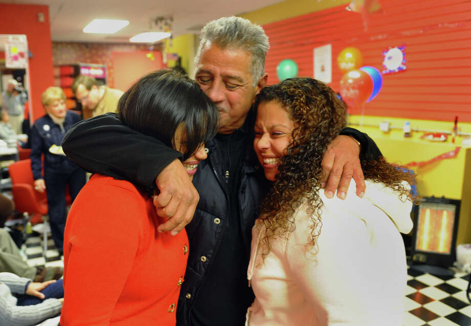 "Alberto ""Tito"" Ayala puts his arms around his daughters Christina Ayala, left, and Lisa Quinones, after Ayala won the state representative seat in the 128th district, at Ayala's headquarters on East Main Street in Bridgeport, Conn. on Tuesday November 6, 2012. Photo: Christian Abraham / Connecticut Post"