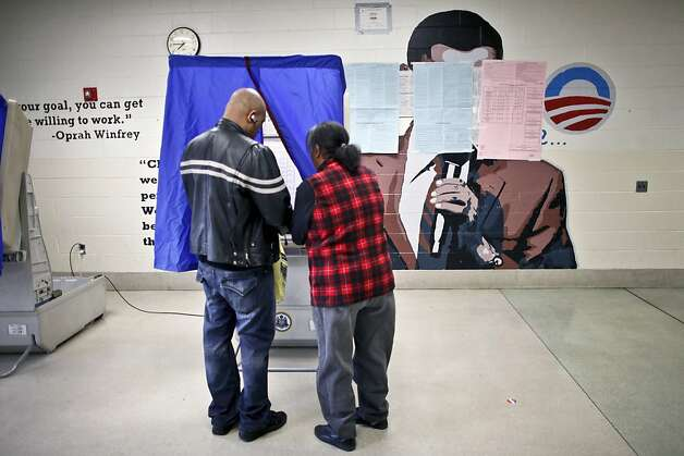 People cast their votes Tuesday, Nov. 6, 2012, at polling location inside the Benjamin Franklin Elementary School in Northeast Philadelphia, where a mural of President Barack Obama painted on a wall behind two voting booths was ordered covered up by a Philadelphia court. The mural had been left uncovered when the polling location opened, but was ordered covered after Republicans filed a complaint. (AP Photo/ Joseph Kaczmarek) Photo: Joseph Kaczmarek, Associated Press