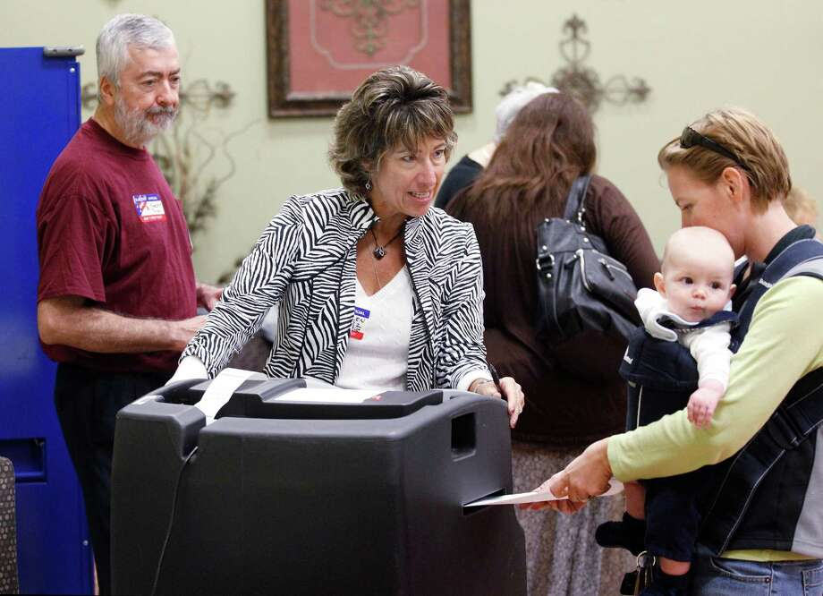 Election Judge Ellen Lopez assists a voter who has her hands full after the ballot scanner jammed Tuesday at the First Baptist Church of Colleyville. Photo: RON T. ENNIS, MBI / The Fort Worth Star-Telegram