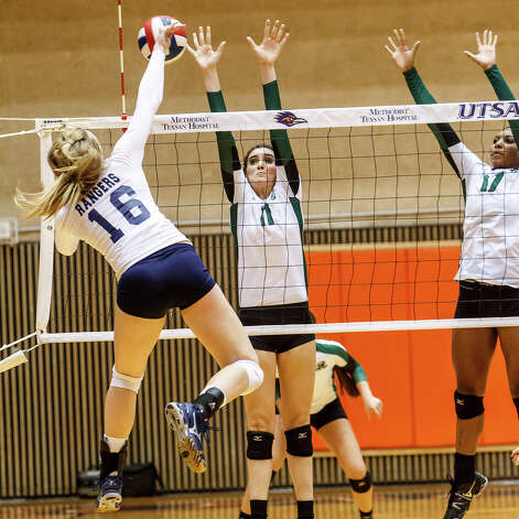 Smithson Valley's Allison Meckel (left) finds an opening through Reagan's Ashlie Reasor (center) and Tarine Grace during their Class 5A third round volleyball match at the UTSA Convocation Center on Nov. 6, 2012.  Smithson Valley won the match in three straight sets: 25-23, 25-21 and 25-19.  MARVIN PFEIFFER/ mpfeiffer@express-news.net Photo: MARVIN PFEIFFER, Express-News / Express-News 2012