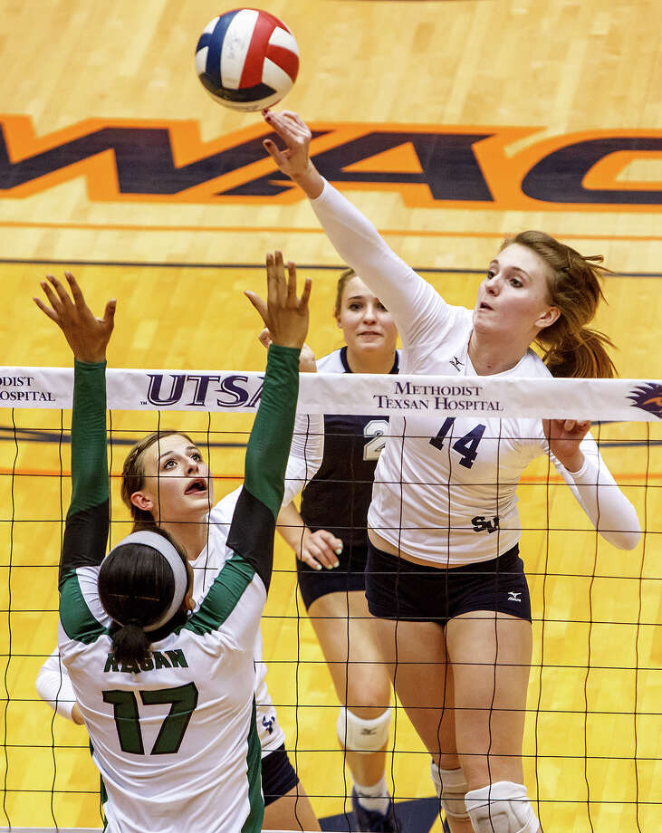 Smithson Valley's Allison Grona (right) shoots over Reagan's Tarine Grace as Emily Medlin (top left) and Meghan Uecker look on during their Class 5A third round volleyball match at the UTSA Convocation Center on Nov. 6, 2012.  Smithson Valley won the match in three straight sets: 25-23, 25-21 and 25-19.  MARVIN PFEIFFER/ mpfeiffer@express-news.net Photo: MARVIN PFEIFFER, Express-News / Express-News 2012