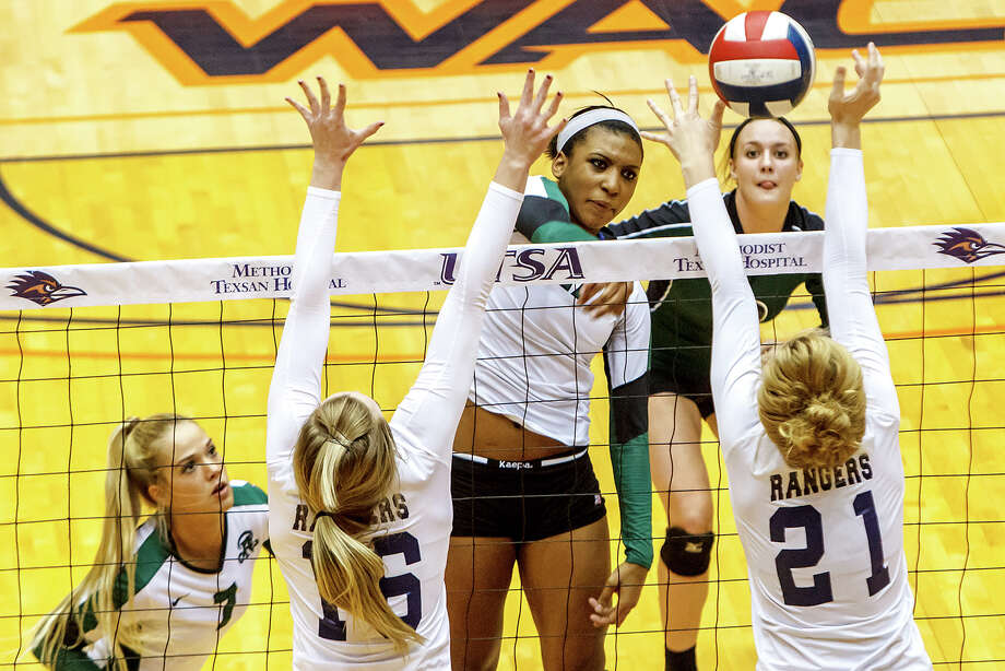 Reagan's Tarine Grace (center) gets a shot past Smithson Valley's McKinlee Boss (right) and Allison Meckel as Katie Medell (top right) and Bailey Shurbet look on during the first set of their Class 5A third round volleyball match at the UTSA Convocation Center on Nov. 6, 2012.  Smithson Valley won the match in three straight sets: 25-23, 25-21 and 25-19.  MARVIN PFEIFFER/ mpfeiffer@express-news.net Photo: MARVIN PFEIFFER, Express-News / Express-News 2012