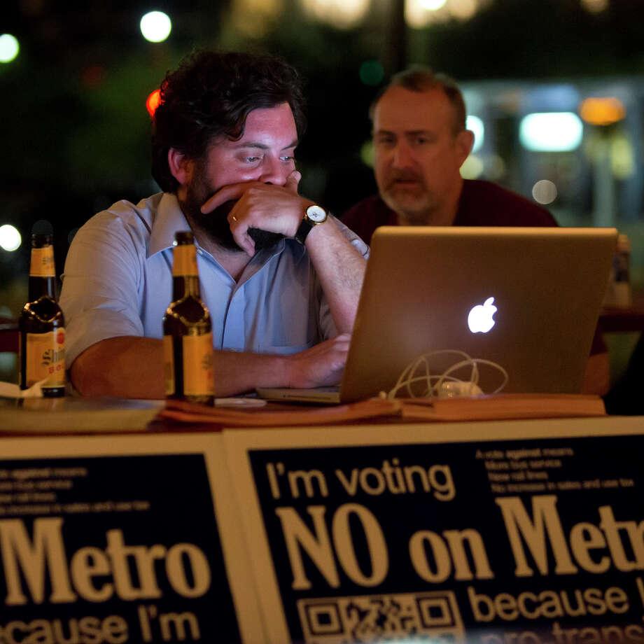Jay Blazek Crossley, left, who works for Houston Tomorrow, and Jon Boyd follow returns for the Metro referendum at a pro-transit party at Natachee's restaurant. Photo: Bruce Bennett, Staff / Houston Chronicle