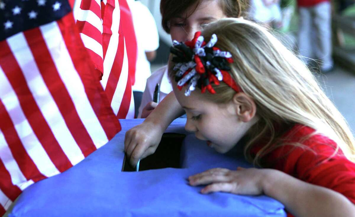 Haeven Smith, 6, casts her vote on the HISD bonds as the first- through third-graders in teacher Luz Torres' class learned about voting as part of their social studies civic lesson at Garden Oaks Elementary School.