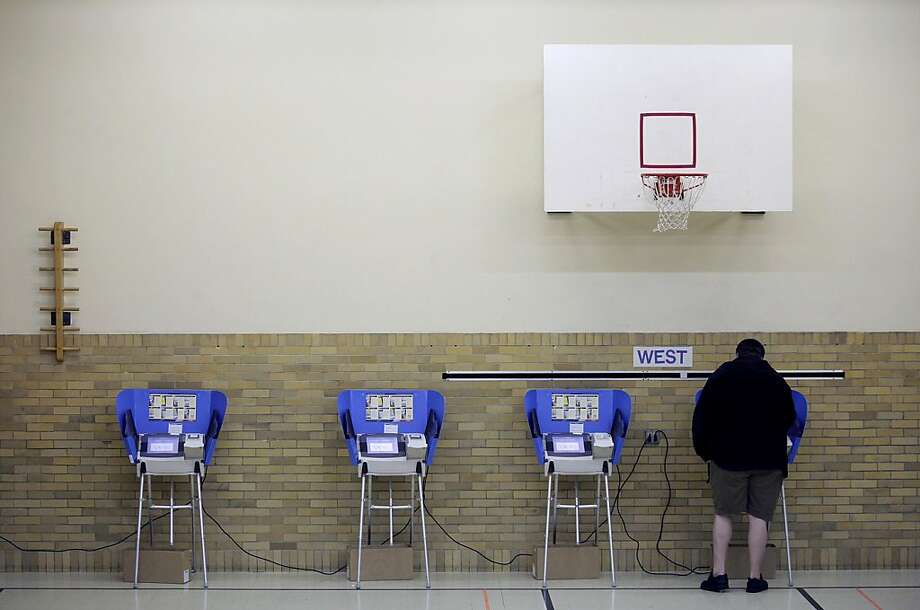 BOWLING GREEN, OH  - NOVEMBER 6: A man casts his ballot using an electronic voting machine November 6, 2012 at an elementary school in Bowling Green, Ohio. Voting is underway in the US presidential election in the battleground state of Ohio. Recent polls show that U.S. President Barack Obama and Republican presidential candidate Mitt Romney are in a tight race. (Photo by J.D. Pooley/Getty Images) Photo: J.D. Pooley, Getty Images