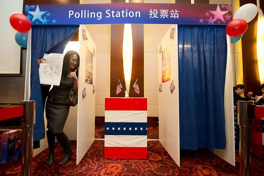 A woman poses after placing a mock vote during a US presidential election results event organised by the US embassy in Beijing on November 7, 2012. Barack Obama and Mitt Romney steeled themselves for nervous hours as polls closed in the first of the key swing states that will decide their tight and bitter White House duel. AFP PHOTO / Ed JonesEd Jones/AFP/Getty Images Photo: Ed Jones, AFP/Getty Images