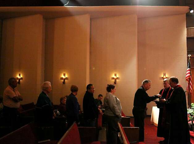 Paul Wallace takes communion from Senior Pastor Rev. Mike Albert, right, and Associate Pastor Will Smith during an Election Day Communion at Yale Avenue Christian Church in Tulsa, Okla., on Tuesday Nov. 6, 2012.JOHN CLANTON/Tulsa World(AP Photo/Tulsa World, John Clanton)  ONLINE OUT; TV OUT; TULSA OUT Photo: John Clanton, Associated Press