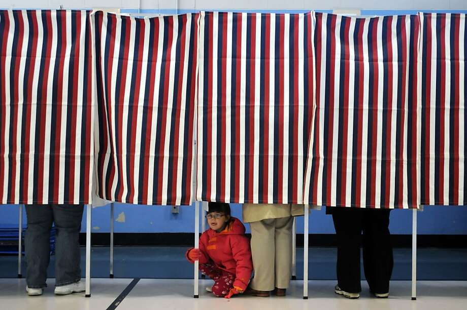 MANCHESTER, NH - NOVEMBER 6:  A young girl looks out from a voting booth as her mother casts her ballot at the Bishop Leo O'Neil Youth Center on November 6, 2012 in Manchester, New Hampshire. The swing state of New Hampshire is recognised to be a hotly contested battleground that offers 4 electoral votes, as recent polls predict that the race between U.S. President Barack Obama and Republican presidential candidate Mitt Romney remains tight.  (Photo by Edward Linsmier/Getty Images) Photo: Darren McCollester, Getty Images