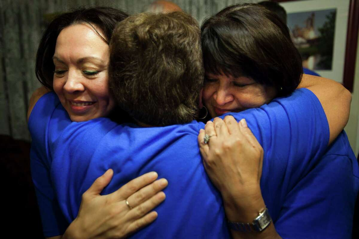 Ali Templer, left, daughter of Sen. Mario Gallegos, Connie Sanchez and Theresa Gallegos, the late senator's widow, embrace after the election results came in Tuesday at the Democrat's watch party.