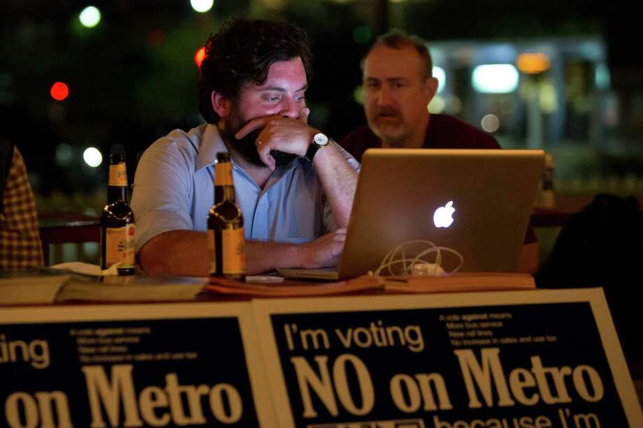 Jay Blazek Crossley and Jon Boyd  follow Tuesday's election returns for the Metro referendum at an election night pro-transit party held at Natachee's, 3622 Main Street, November 6, 2012.  Crossley works at Houston Tomorrow, a nonprofit organization which opposed the referendum. Photo: Bruce Bennett, For The Chronicle / Houston Chronicle