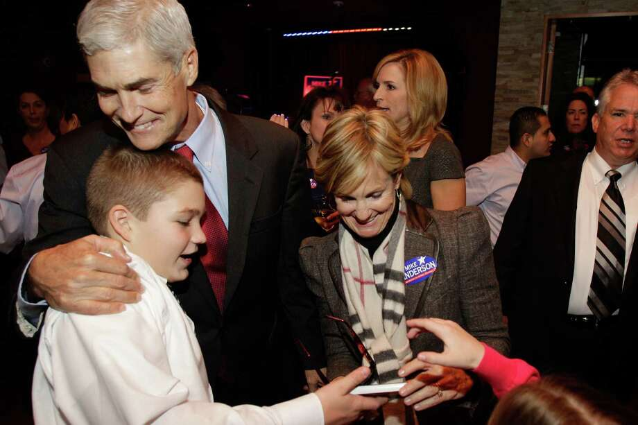 Republican candidate for Harris County district attorney Mike Anderson hugs his son Sam,11, as he and his sister, Jan Bailey, right, and wife, Devon Anderson, back right, greet supporters during election watching party Gloria's, 2616 Louisiana, Tuesday, Nov. 6, 2012, in Houston. Photo: Melissa Phillip, Houston Chronicle / © 2012 Houston Chronicle