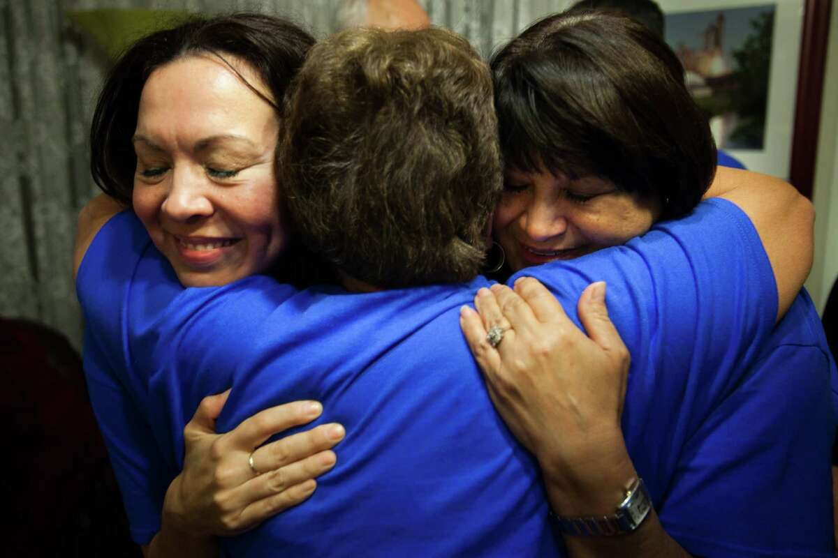 Ali Templer, left, the daughter of Senator Mario Gallegos, hugs Connie Sanchez, center, and Theresa Gallegos, right, the wife of Senator Gallegos, after positive election results come in at a watch party for the late state senator on Nov. 6, 2012 in Houston. Gallegos, who passed away in October, is still on the November ballot. He must win in order to keep his seat in Democratic hands and allow the residents of Senate District 6 to elect his replacement.