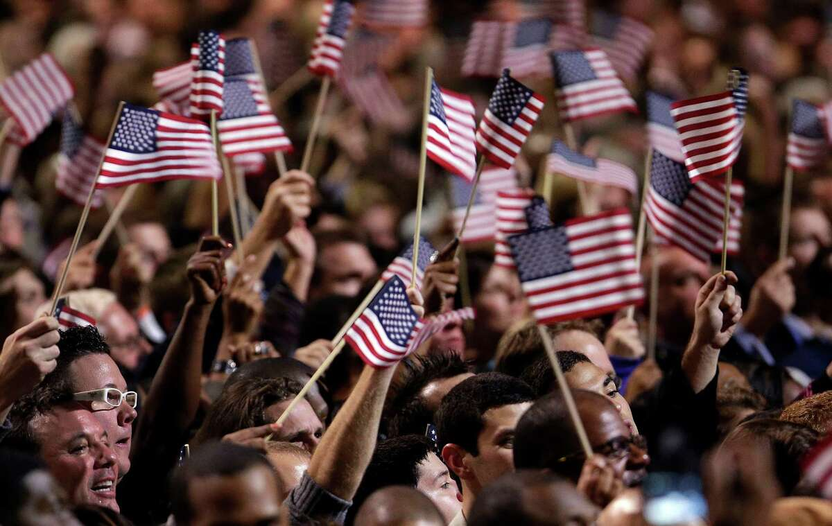 Supporters wave flags during President Barack Obama's election night party Tuesday, Nov. 6, 2012, in Chicago. President Obama defeated Republican challenger former Massachusetts Gov. Mitt Romney. (AP Photo/M. Spencer Green)