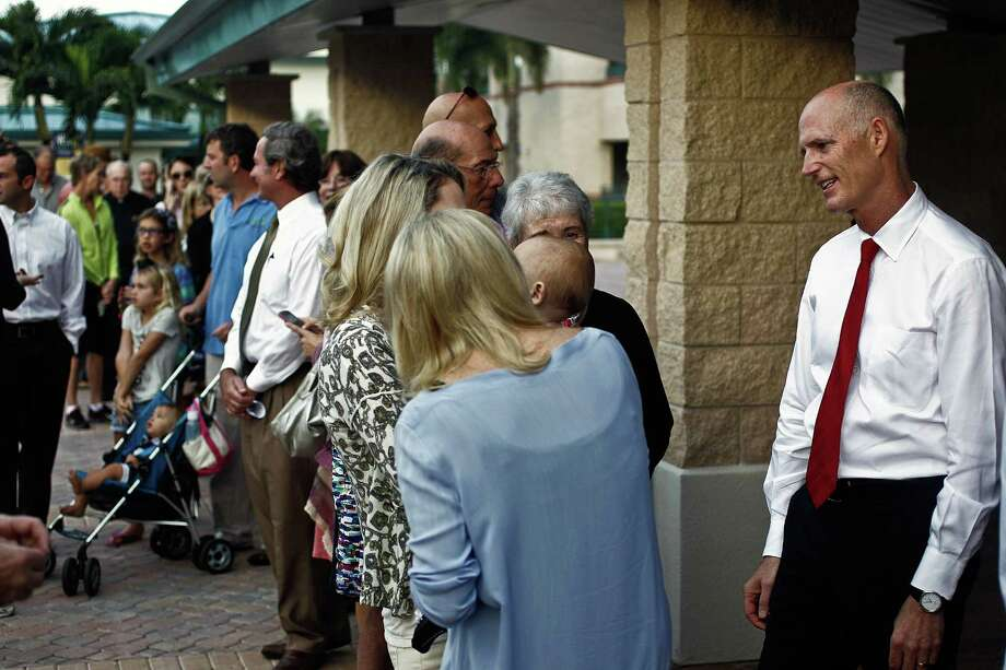 Gov. Rick Scott, right, chats with his family and fellow voters while they wait in line to vote at St. Ann's Catholic Church, Tuesday, Nov. 6, 2012, in Naples, Fla. (AP Photo/Naples Daily News, Scott McIntyre) FORT MYERS OUT Photo: Scott McIntyre