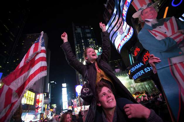 People celebrate the news that U.S. President Barack Obama has won re-election in Times Square in New York, U.S., in the early morning on Wednesday, Nov. 7, 2012. Obama, the post-partisan candidate of hope who became the first black U.S. president, won re-election today by overcoming four years of economic discontent with a mix of political populism and electoral math. Photo: Scott Eells, Bloomberg / © 2012 Bloomberg Finance LP