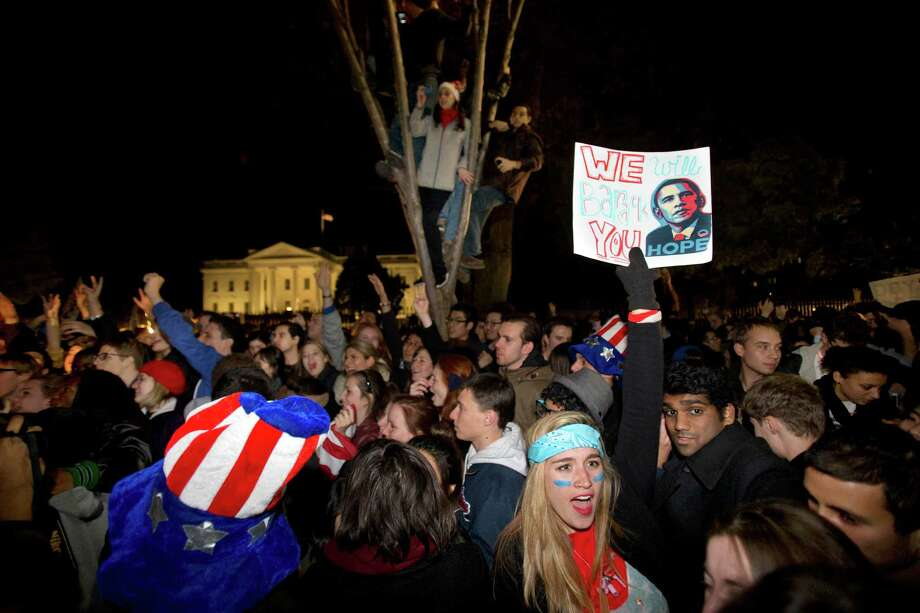 "Kelly Rodgers, 18, of Philadelphia, holds a sign saying ""We Will Barack You"" as people celebrate outside of the White House after President Barack Obama won re-election against Mitt Romney in the presidential election on Pennsylvania Avenue in Washington, Wednesday, Nov. 7, 2012. Photo: Jacquelyn Martin, Associated Press / AP"