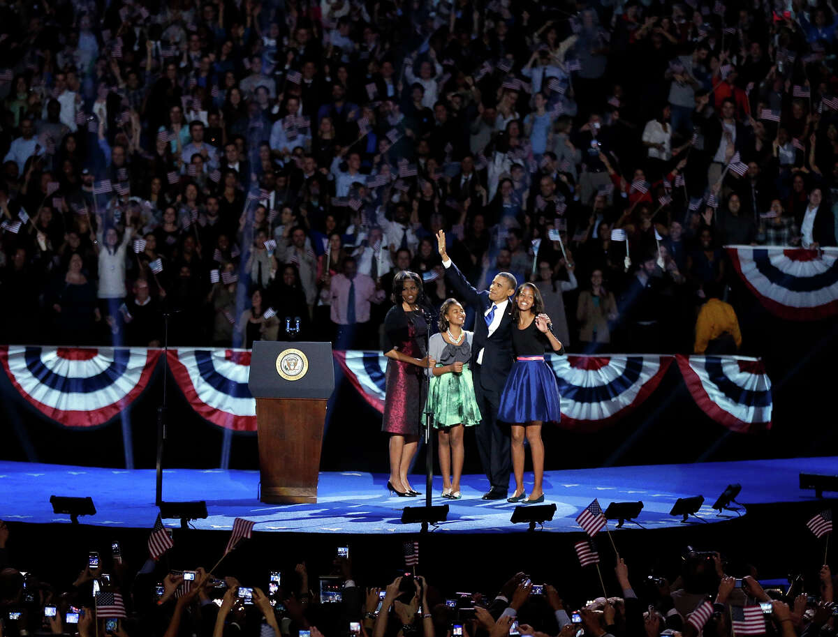 President Barack Obama waves as he walks on stage with first lady Michelle Obama and daughters Malia and Sasha at his election night party Wednesday, Nov. 7, 2012, in Chicago. President Obama defeated Republican challenger former Massachusetts Gov. Mitt Romney.