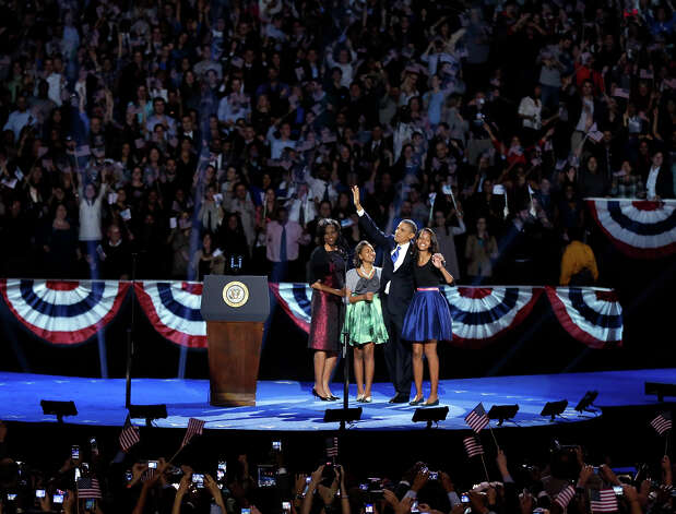 President Barack Obama waves as he walks on stage with first lady Michelle Obama and daughters Malia and Sasha at his election night party Wednesday, Nov. 7, 2012, in Chicago. President Obama defeated Republican challenger former Massachusetts Gov. Mitt Romney. Photo: AP