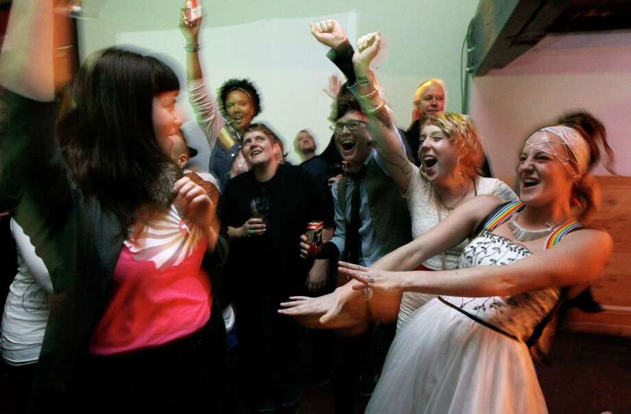 Judea Ezell, right, wearing a wedding dress, and Shena Lee, left, join other supporters of Washington state's Referendum 74, which would legalize same-sex marriage, in a celebratory dance, Tuesday, Nov. 6, 2012, at a bar in Seattle's Capitol Hill neighborhood. Photo: AP