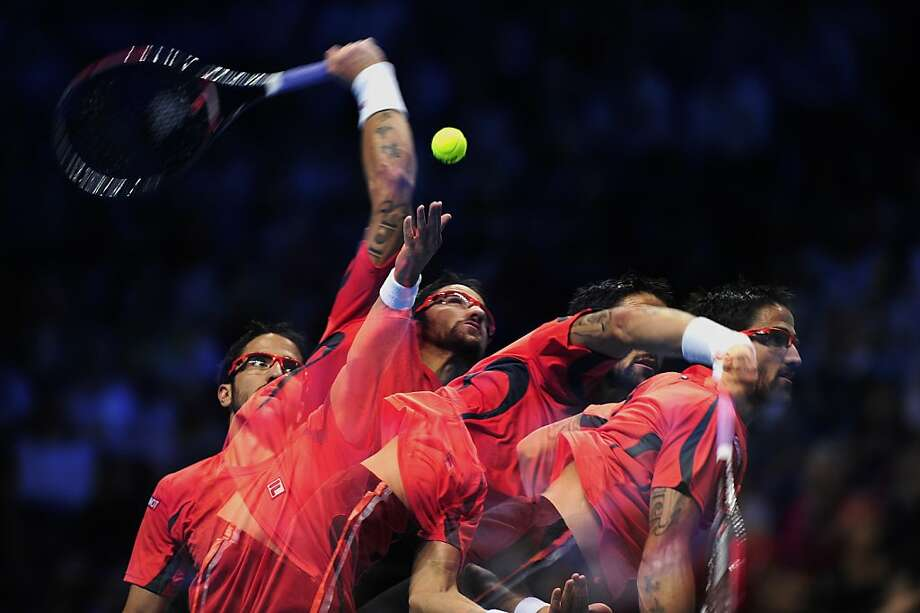 In this multiple exposure image Serbia's Janko Tipsarevic serves against Switzerland's Roger Federer during their group B singles match in the round robin stage on the second day of the ATP World Tour Finals tennis tournament in London on November 6, 2012. Photo: Glyn Kirk, AFP/Getty Images