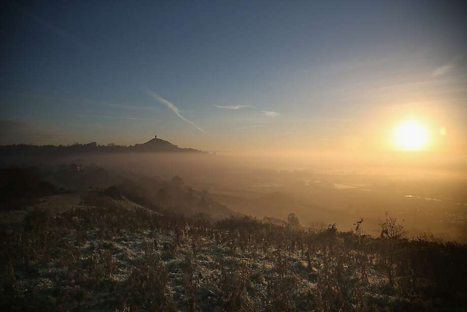 Mist lingers at the foot of Glastonbury Tor as the sun rises over the Somerset Levels on November 6, 2012 in Glastonbury, England. Parts of the UK have experienced one of the coldest starts to November for many years and the Met Office is predicting that the coming winter could be a colder one than average. Photo: Matt Cardy, Getty Images