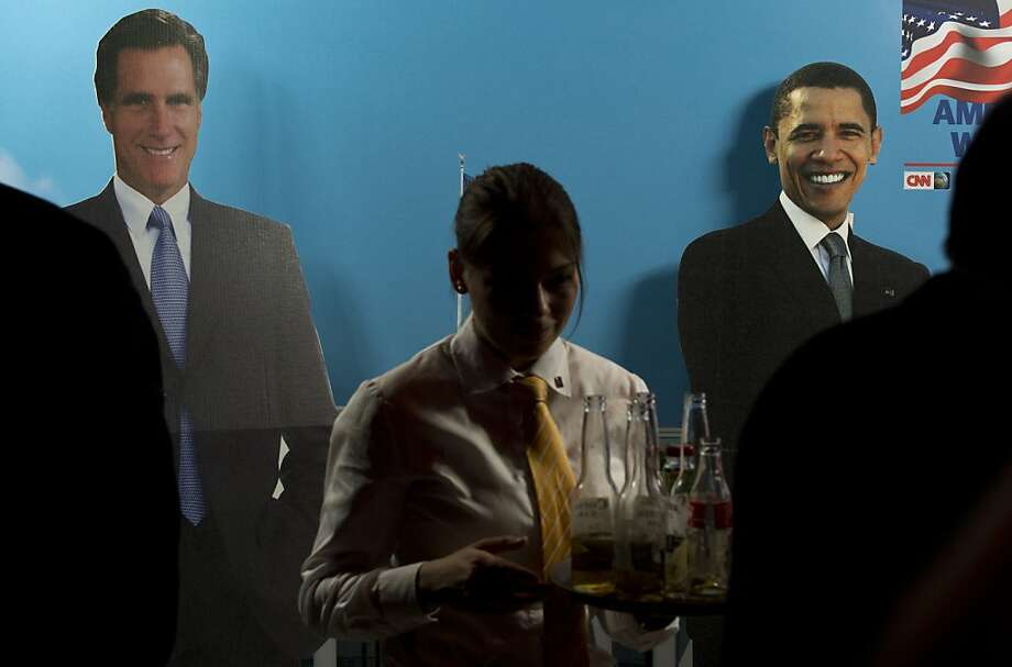 A waitress walks past cardboard cutouts of US President Barack Obama (R) and presidential candidate Mitt Romney (L) at a US election party at the headquarters of German media giant Bertelsmann in Berlin, on November 6, 2012. Photo: John Macdougall, AFP/Getty Images