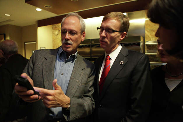 Rob McKenna, right, checks the early election results during the Washington State Republican Party's 2012 Election Night Party Nov. 6, 2012 at the Bellevue Hyatt in Bellevue, Wash. (Photo by Cliff DesPeaux for seattlepi.com) Photo: CLIFF DESPEAUX, / / FOR SEATTLEPI.COM