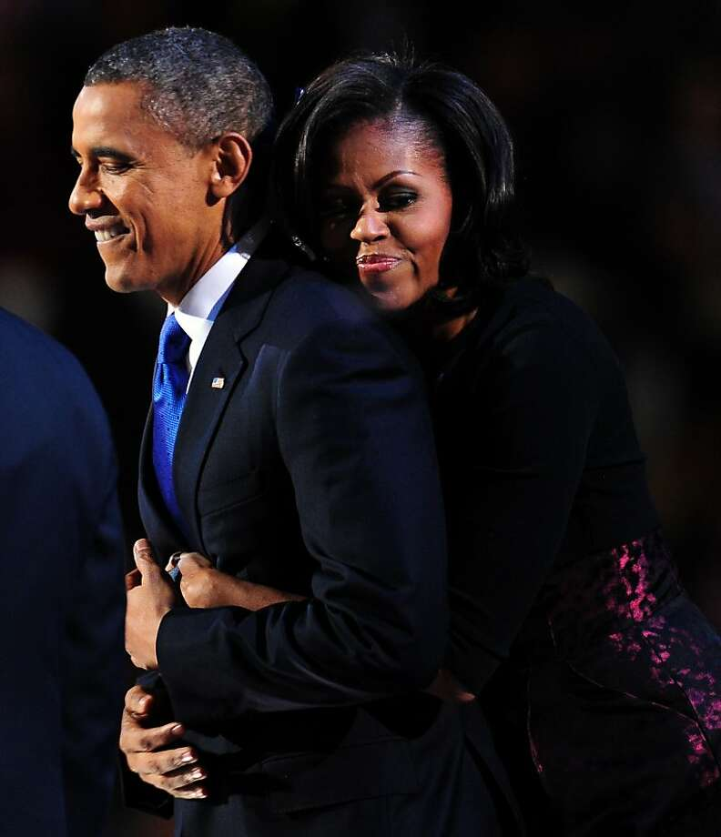 US President Barack Obama is embraced by First Lady Michelle Obama on stage after winning the 2012 US presidential election  November 7, 2012 in Chicago, Illinois.  Obama swept to a emphatic re-election win over Mitt Romney,  forging new history by transcending a dragging economy and the stifling unemployment which haunted his first term.   AFP PHOTO / Robyn BeckROBYN BECK/AFP/Getty Images Photo: Robyn Beck, AFP/Getty Images
