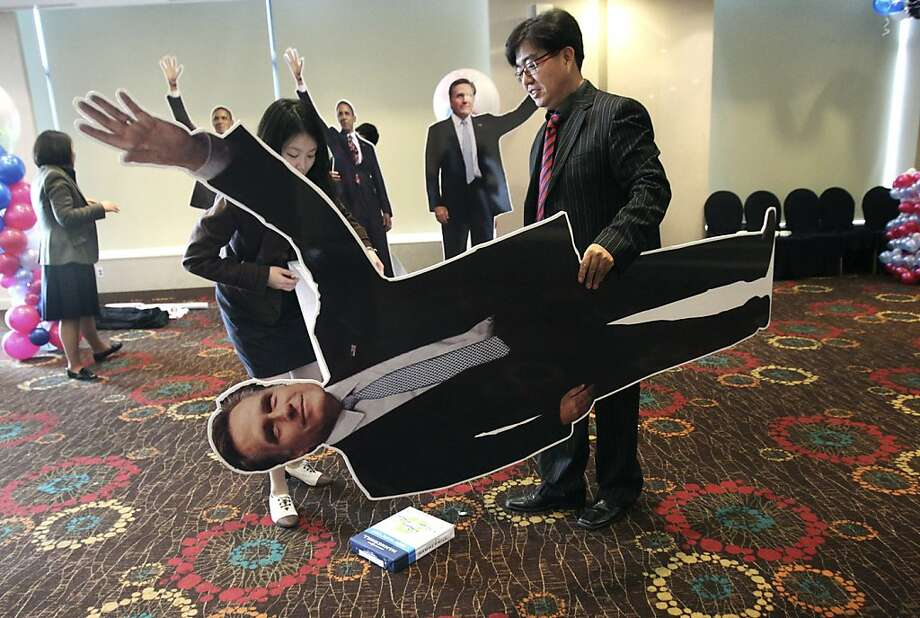 An employee of the U.S. Embassy carries a cutout of Republican presidential candidate, former Massachusetts Gov. Mitt Romney, following an election event hosted by the U.S. Embassy in Seoul, South Korea, Wednesday, Nov. 7, 2012.  President Barack Obama won re-election Tuesday night despite a fierce challenge from Republican Mitt Romney, prevailing in the face of a weak economy and high unemployment that encumbered his first term and crimped the middle class dreams of millions.  (AP Photo/Ahn Young-joon) Photo: Ahn Young-joon, Associated Press