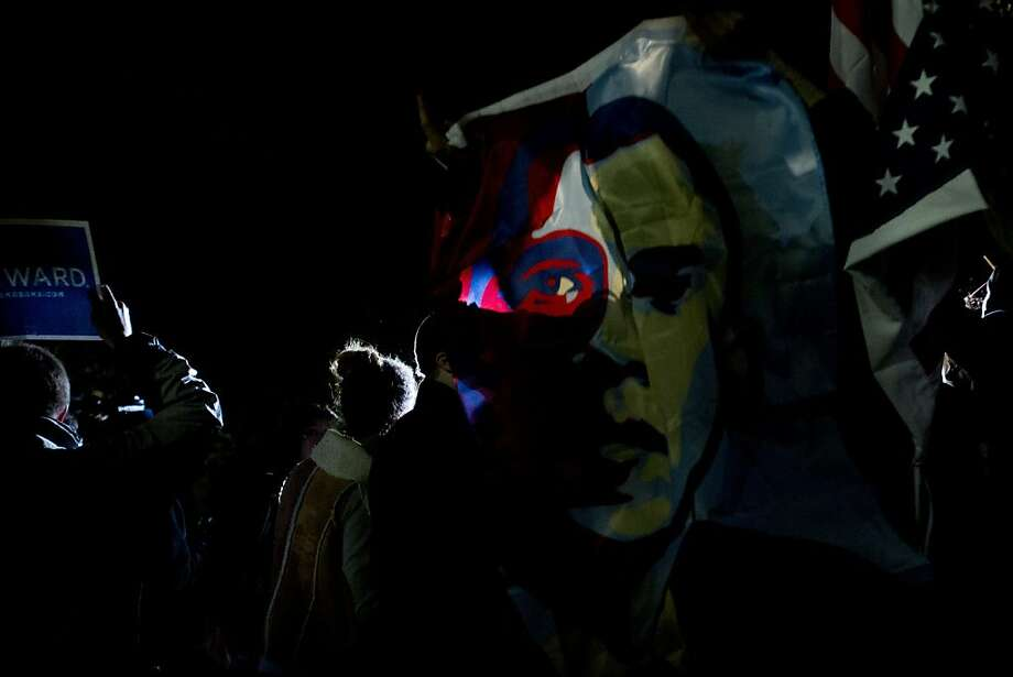 Light shines through a flag of President Barack Obama as people celebrate his re-election outside of the White House, on Pennsylvania Avenue in Washington in the early morning on Wednesday, Nov. 7, 2012. (AP Photo/Jacquelyn Martin) Photo: Jacquelyn Martin, Associated Press