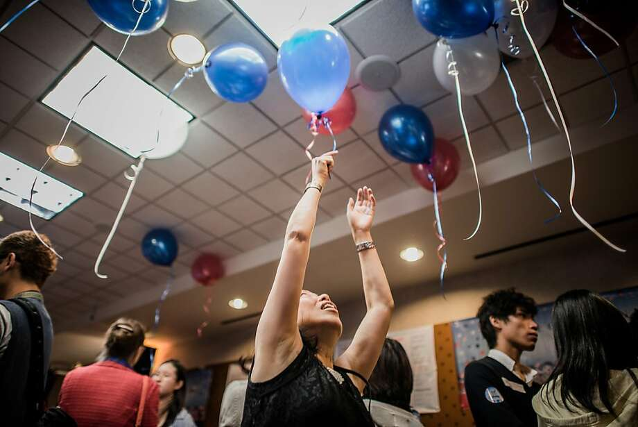 A woman reaches for a balloon during an election day at the US consulate in Hong Kong on November 7, 2012.   President Barack Obama swept to re-election, forging history again by transcending a slow economic recovery and the high unemployment which haunted his first term to beat Republican Mitt Romney.  AFP PHOTO / Philippe LopezPHILIPPE LOPEZ/AFP/Getty Images Photo: Philippe Lopez, AFP/Getty Images
