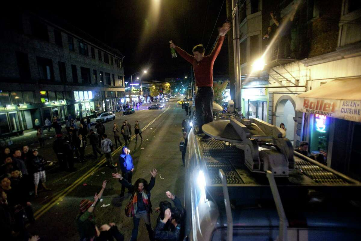 A man climbs on top of a television news truck with a bottle of champagne as a spontaneous party erupts in the intersection of East Pike Street and 10th Avenue after Barack Obama was announced as the winner, Referendum 74 appeared to be passing and a measure to legalize marijuana also seemed to be passing on Election Day, Tuesday, November 6, 2012.